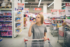 Curious Woman in The Supermarket . Young girl in a market store with  shopping thinking what to buy Stock Images