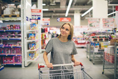 Curious Woman in The Supermarket . Young girl in a market store with  shopping thinking what to buy Royalty Free Stock Images