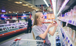 Curious Woman in The Supermarket . Young girl in a market store with  shopping thinking what to buy Stock Photos