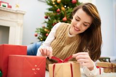 Curious Woman Unwrapping Christmas Gift Box. Portrait of beautiful young woman with charming smile lying on cozy carpet of living room decorated for Christmas Royalty Free Stock Photo