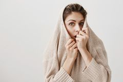Curious woman wants to hear rest of scary story. Charming adult caucasian female pulling sweater on face and hiding it. Peeking over collar with shocked Stock Photo