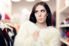 Curious Woman Wearing White Fur Coat in Fashion Store. Funny girl looking for Christmas presents in a clothing store Royalty Free Stock Images