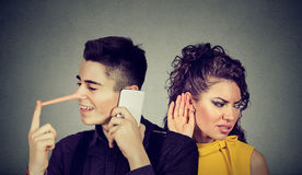 Curious worried woman secretly listening to a happy man liar talking on mobile phone with his lover Royalty Free Stock Image