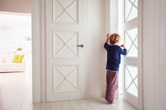 Curious young boy looks into the ajar door Royalty Free Stock Photo