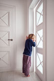 Curious young boy looks into the ajar door Royalty Free Stock Photography