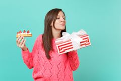 Curious young girl in knitted pink sweater hold eclair cake, red striped present box with gift ribbon isolated on blue. Background. Valentine`s Women`s Day royalty free stock image