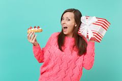 Curious young girl in knitted pink sweater hold eclair cake, red striped present box with gift ribbon isolated on blue. Background. Valentine`s Women`s Day royalty free stock photo
