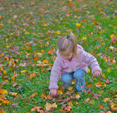 Curious young girl in the park. Innocent parenthood image of a curious young girl in the playground picking up a pine cone Stock Photos
