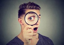 Curious young man looking through a magnifying glass. Curious man looking through a magnifying glass royalty free stock photo