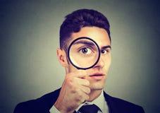Curious young man looking through a magnifying glass. Curious young business man looking through a magnifying glass suspiciously royalty free stock photos