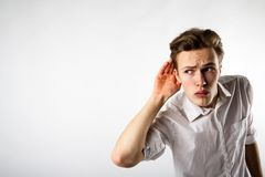Curious young man in white. Is eager to know all the gossip stock image