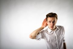 Curious young man in white. Is eager to know all the gossip royalty free stock images