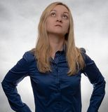 Curious young woman in casual blue shirt looking up royalty free stock photography