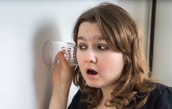Curious young woman is listening and spying on neighbours behind wall.  Royalty Free Stock Photography