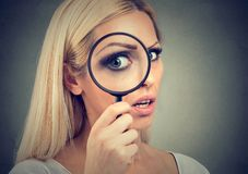 Curious young woman looking through a magnifying glass. Amazed curious blonde woman looking through a magnifying glass isolated on gray background royalty free stock photo