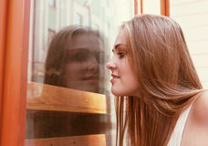 Curious Young Woman Looking Through Window. Outdoors Stock Photography