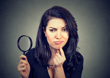 Curious young woman with magnifying glass royalty free stock photos