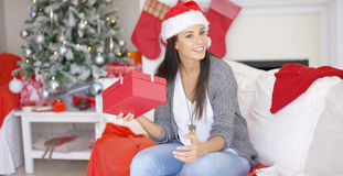 Curious young woman shaking a Christmas gift Royalty Free Stock Photos