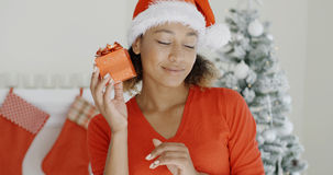 Curious young woman shaking her Christmas gift Royalty Free Stock Images