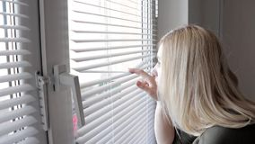 Curious young woman spying, peeking through the blinds in her home.  stock footage