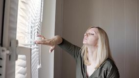 Curious young woman spying, peeking through the blinds in her home.  stock video footage