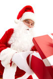 Curiousity. Photo of happy Santa Claus looking into red giftbox in isolation Royalty Free Stock Photo
