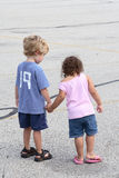 Curiousity. Two kids holding hands have stopped to look at something on the sidewalk Stock Images