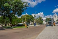 CURITIBA, БРАЗИЛИЯ - 12-ОЕ МАЯ 2016: arround пешеходов идя автобусная станция окруженная большими деревьями Стоковое Фото