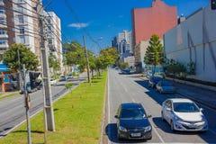 CURITIBA, BRASIL - 12 DE MAIO DE 2016: dois carros que esperam na interseção, cargo do cabo situado no passeio médio Foto de Stock