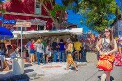 CURITIBA, BRAZILIË - MEI 12, 2016: niet geïdentificeerde mensen die wat voedsel kopen bij een kleine die tribune in een hoek dich Royalty-vrije Stock Foto