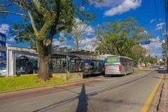 CURITIBA, EL BRASIL - 12 DE MAYO DE 2016: pasajeros que consiguen en un autobús público, árbol grande situado al lado del término Fotografía de archivo libre de regalías