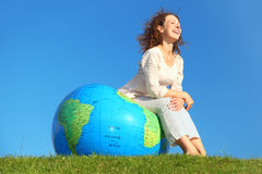 Curl woman sitting on inflatable globe Stock Photos