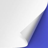 Curled corner of White paper with shadow on Blue Background Stock Photo