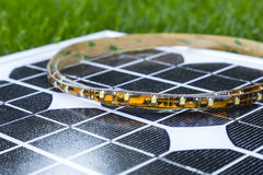 Curled LED strip on photovoltaic solar panel Royalty Free Stock Photos