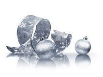 Silver ribbon and Christmas balls. Curled silver ribbon and Christmas balls on white background stock photos