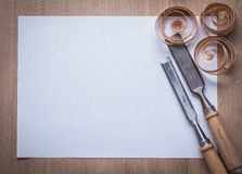 Curled wooden shavings firmer chisels and blank sheet of paper o Stock Image