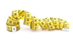 Curled yellow measuring tape Royalty Free Stock Photos