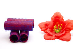 Curler with hibiscus blossom. On white background Royalty Free Stock Image