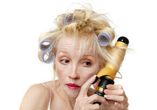 Curler Woman. A blonde woman with lavender curlers in her hair, using a curling iron.  Bad hair day Royalty Free Stock Image