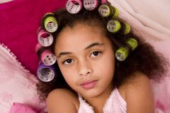 Curlers. Adorable mulatto girl in her bedroom wearing pajamas and colorful curlers stock photo