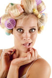 Curlers hair. A woman with curlers in her hair and her hands by her face stock photography