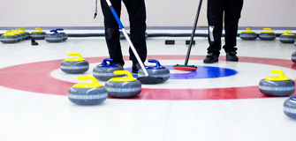 Curling. Two players with brooms on the ice, determining the strategy during a curling game Stock Images