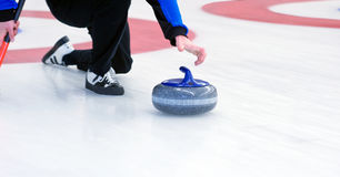 Curling. Player delivering a stone on a  rink, sliding over the ice Stock Photos