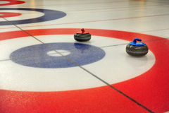 Curling. Colored stones glide over the ice Royalty Free Stock Images