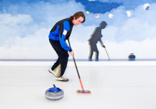 Curling brooming. Curling player influencing the curvature of a stone being delivered with his broom Royalty Free Stock Photo