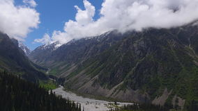 Curling clouds above high mountains and river valley 4K pan time lapse stock video footage