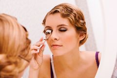 Curling eyelashes. Image of pretty female looking in mirror while curling her eyelashes Royalty Free Stock Photos