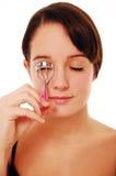 Curling eyelashes. Teenager curling eyelashes isolated on white stock photography