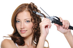 Curling Female Brunette Hair With Roller Stock Image
