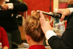 Curling hair. Attractive young Caucasian blonde woman having hair styled for special event Stock Images